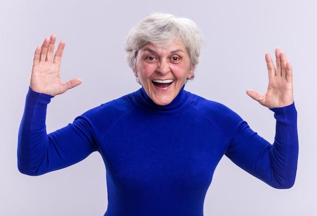 Ältere frau im blauen rollkragenpullover, die glücklich und aufgeregt mit erhobenen armen über weiß in die kamera schaut