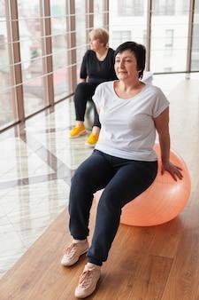 Ältere frau im fitnessstudio am ball