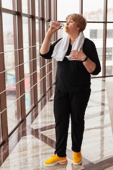 Ältere frau im fitnessstudio feuchtigkeitsspendend