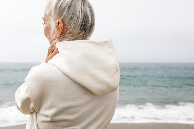 Ältere frau im hoodie, die am strand sich entspannt