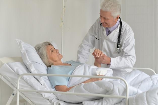 Ältere frau im krankenhaus mit fürsorglichem arzt