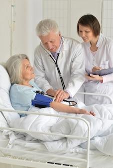 Ältere frau im krankenhaus mit fürsorglichen ärzten