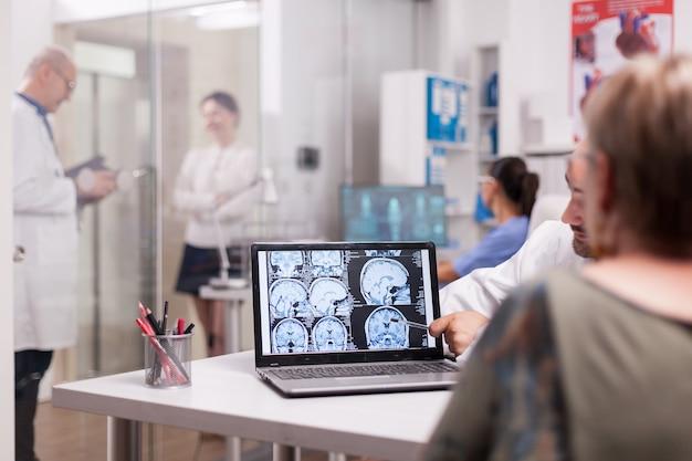 Ältere frau im krankenhausbüro, die sich den ct-scan des gehirns ansieht, während sie mit dem arzt über die diagnose spricht. kranke junge frau und älterer mediziner mit grauem haar im klinikkorridor.