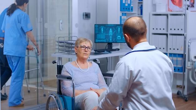 Ältere frau im rollstuhl beim arzttermin in der genesungsklinik. älterer patient im ruhestand, der medizinische beratung und behandlung in einem modernen krankenhaus sucht, behindertenhilfe, behindertenkonsul