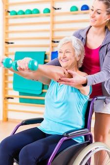 Ältere frau im rollstuhl, der physiotherapie tut