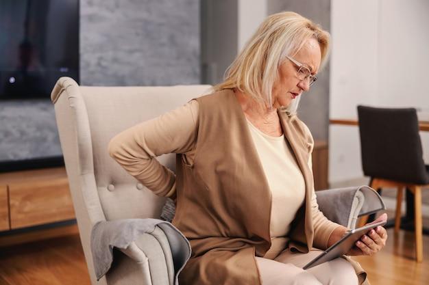 Ältere frau im schmerz, die in ihrem stuhl zu hause sitzt