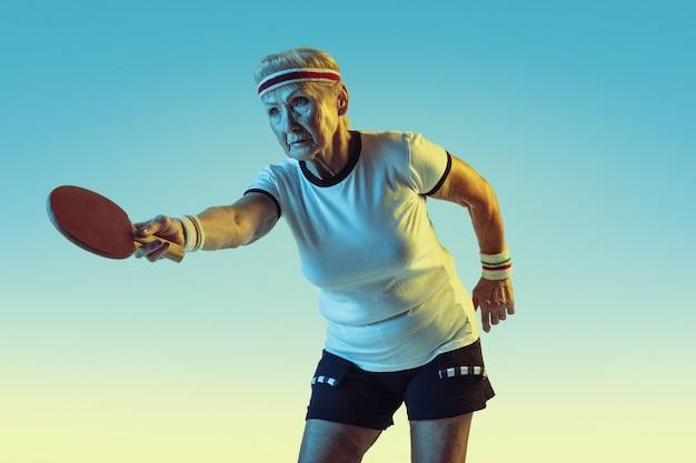 Ältere frau im sportbekleidungstraining im tischtennis auf gradientenhintergrund, neonlicht. Kostenlose Fotos