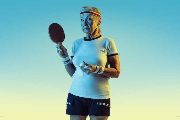 Ältere frau im sportbekleidungstraining im tischtennis auf gradientenhintergrund, neonlicht.