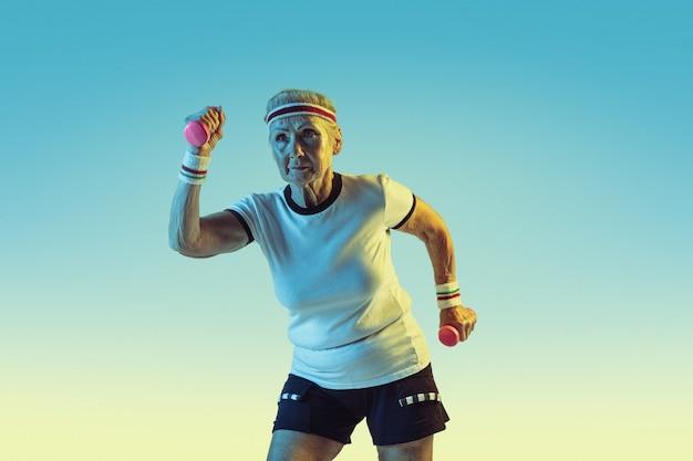 Ältere frau im sportbekleidungstraining mit gewichten auf gradientenhintergrund, neonlicht. weibliches model in guter form bleibt aktiv. konzept von sport, aktivität, bewegung, wohlbefinden, selbstvertrauen. copyspace.