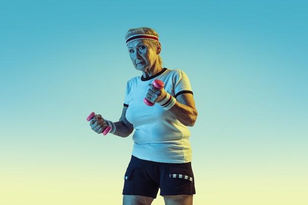 Ältere frau im sportbekleidungstraining mit gewichten auf gradientenwand