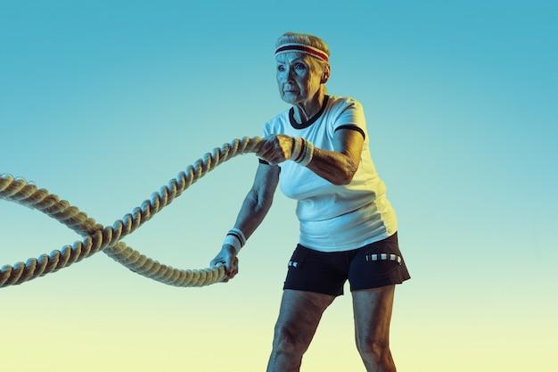 Ältere frau im sportbekleidungstraining mit seilen auf gradientenhintergrund, neonlicht. weibliches model in guter form bleibt aktiv. konzept von sport, aktivität, bewegung, wohlbefinden, selbstvertrauen. copyspace.