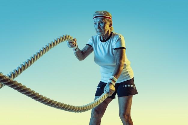 Ältere frau im sportbekleidungstraining mit seilen auf steigungswand
