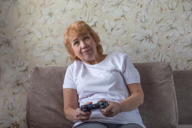 Ältere frau im weißen t-shirt spielt videospiel mit joystick. aufregungsspiele