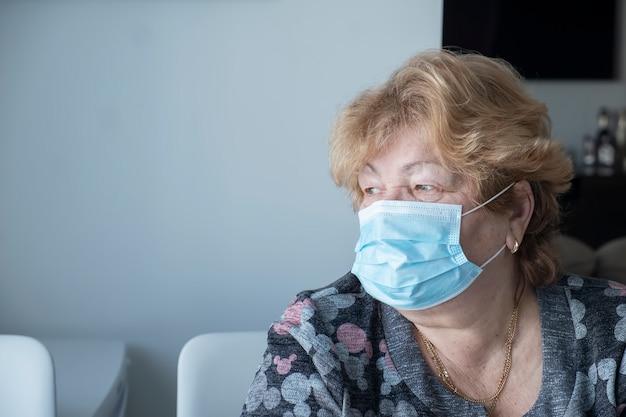 Ältere frau in blauer medizinischer schutzmaske schauen zum fenster. quarantäne