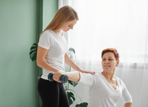 Ältere frau in der koviden genesung, die körperliche übungen mit hantel macht