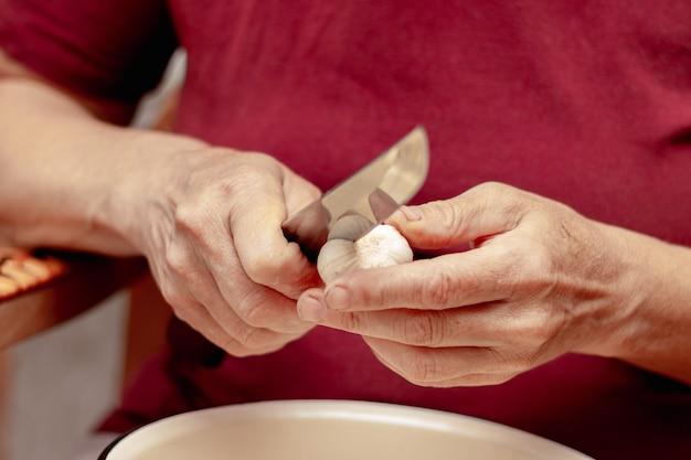 Ältere frau in der küche schneidet knoblauch mit einem küchenmesser. in der küche arbeiten, kochen