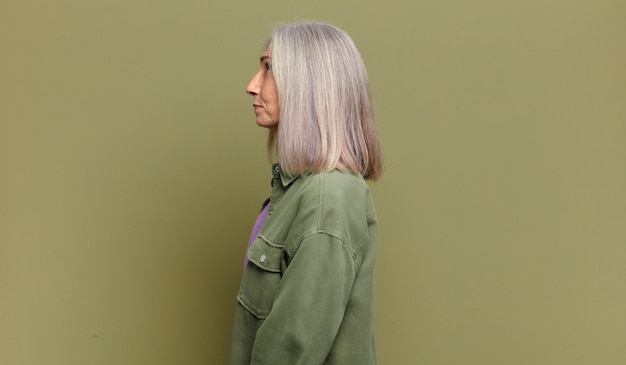 Ältere frau in der profilansicht, die den raum nach vorne kopieren, nachdenken, sich vorstellen oder träumen möchte