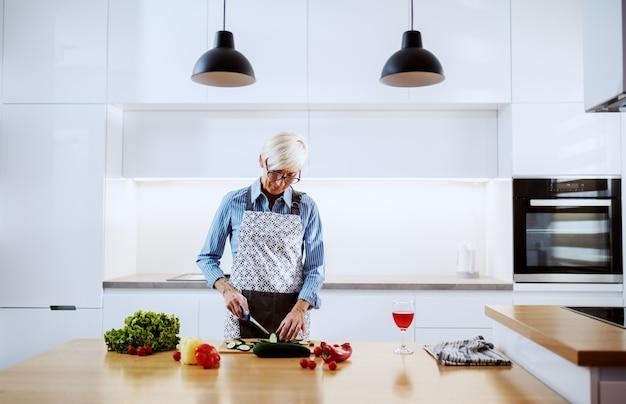 Ältere frau in der schürze, die in der küche steht und gurke schneidet