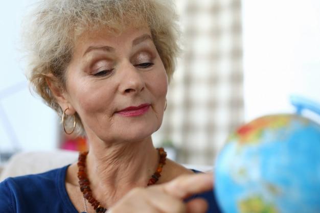 Ältere frau in der wohnung zeigt finger auf globus