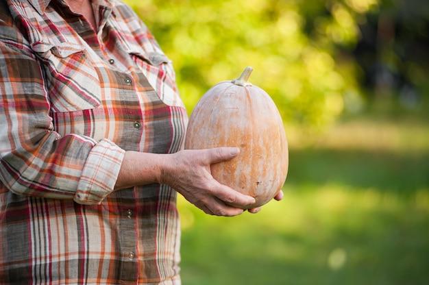 Ältere frau in einem karierten hemd hält einen kürbis im garten.