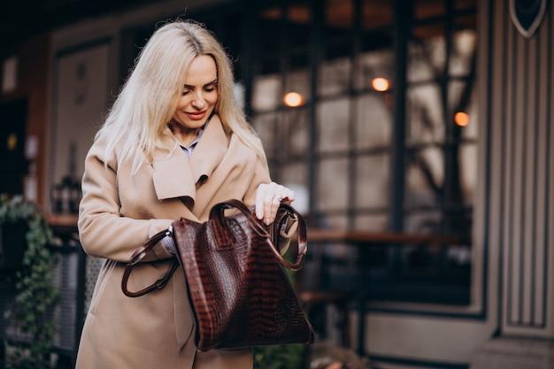 Ältere frau in einem mantel außerhalb des cafés