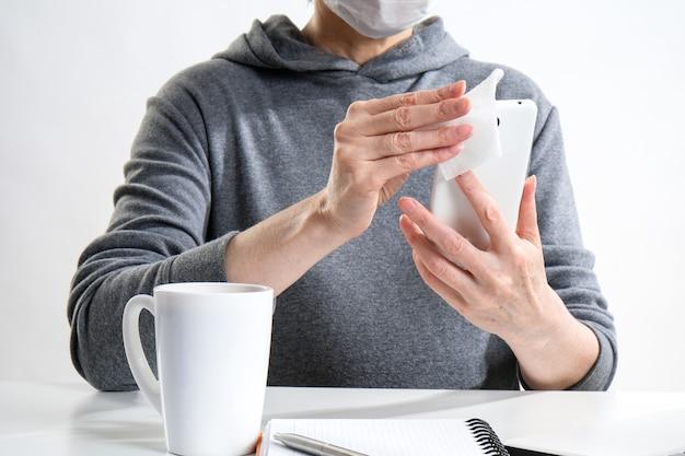 Ältere frau in einer medizinischen schutzmaske arbeitet im büro. eine frau desinfiziert ein mobiltelefon mit einer serviette mit einem antibakteriellen alkoholmittel.