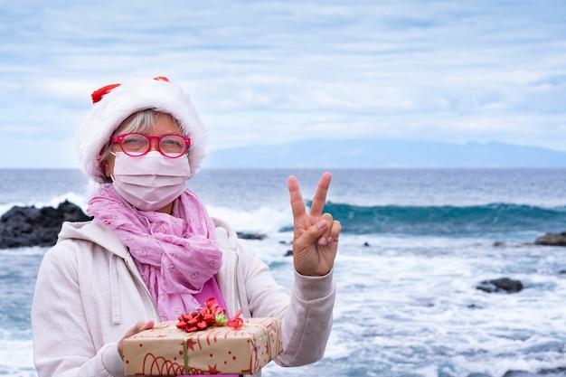 Ältere frau in einer weihnachtsmütze mit einer schutzmaske, die am strand steht und ein weihnachtsgeschenk hält