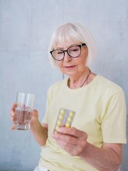 Ältere frau in gläsern, die medizinpillen und ein glas wasser halten