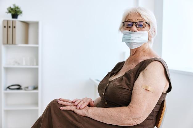 Ältere frau in medizinischer maske, die im krankenhausimpfpass sitzt