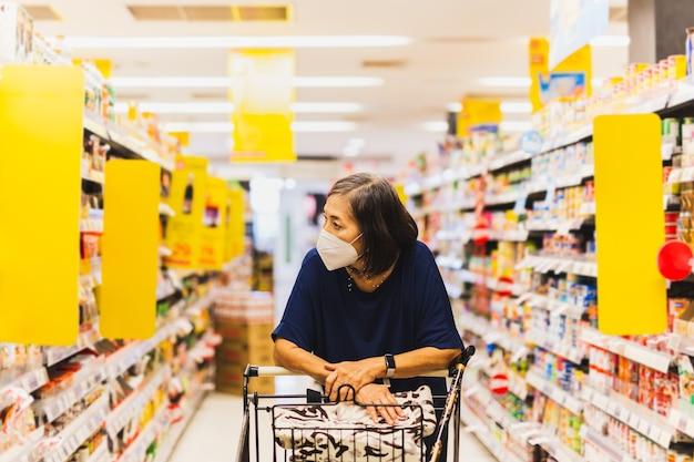 Ältere frau in schutzmaske allein im supermarkt einkaufen supermarket