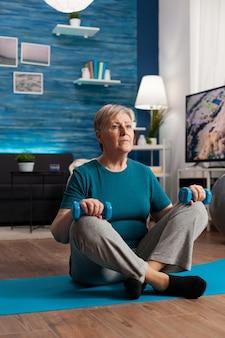 Ältere frau in sportbekleidung, die bauchmuskeln aufwärmt, die gymnastikkörperübungen mit trainingshanteln praktizieren. rentner sitzt auf yogamatte im lotussitz während wellness-routine im wohnzimmer
