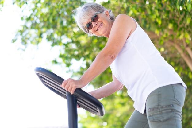 Ältere frau in sportlicher aktivität im öffentlichen park, sitzt auf fahrradausrüstung und macht übungen, lächelt