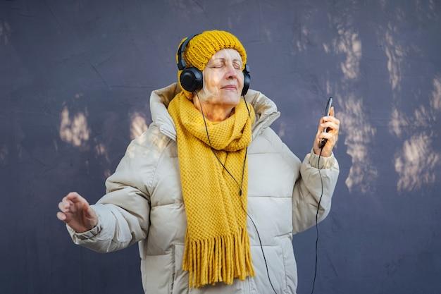 Ältere frau in stylischer oberbekleidung, die musik über kopfhörer hört und tanzt