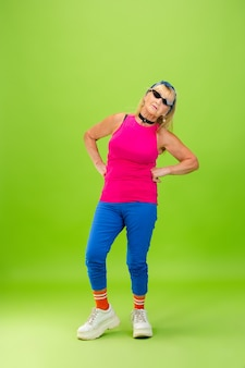 Ältere frau in ultra trendiger kleidung auf hellgrünem hintergrund isoliert