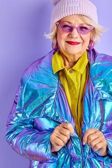 Ältere frau in winterkleidung und sonnenbrille, in modischer ausgefallener kleidung, isoliert über lila raum, vorbereitung für den spaziergang, genießen