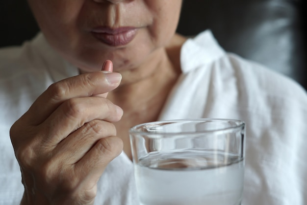 Ältere frau isst medizin und mit pillen und glas wasser zu hause