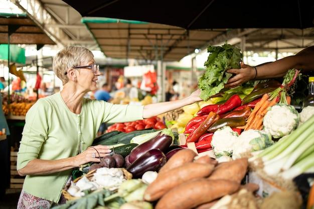 Ältere frau kauft frisches bio-gemüse auf dem marktplatz für gesunde ernährung.