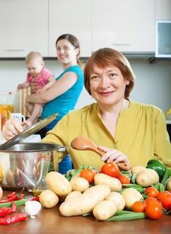Ältere frau kocht veggie mittagessen in der küche