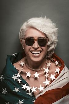 Ältere frau lacht und betrachtet kamera, die in amerikanische flagge eingewickelt ist, die perlen der sterne trägt