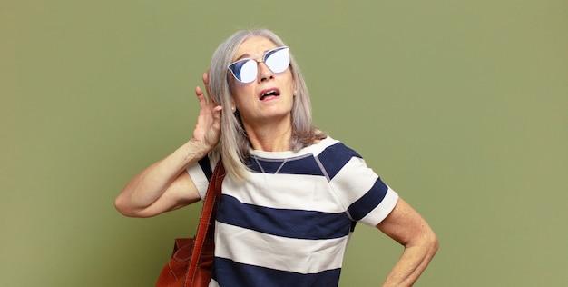 Ältere frau lächelnd, neugierig zur seite schauend, versuchend, klatsch zu hören oder ein geheimnis zu belauschen