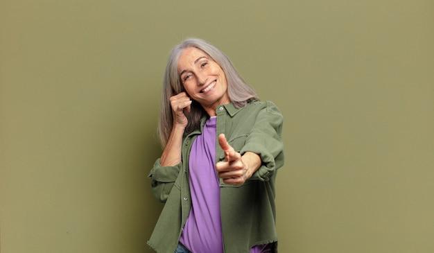 Ältere frau lächelt fröhlich und zeigt nach vorne, während sie einen anruf tätigen, den sie später gestikulieren und am telefon sprechen