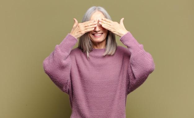 Ältere frau lächelt und fühlt sich glücklich, bedeckt die augen mit beiden händen und wartet auf eine unglaubliche überraschung