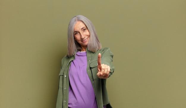 Ältere frau lächelt und sieht freundlich aus, zeigt nummer eins oder zuerst mit der hand nach vorne, zählt herunter