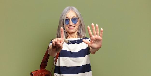 Ältere frau lächelt und sieht freundlich aus, zeigt nummer sechs oder sechste mit der hand nach vorne, countdown
