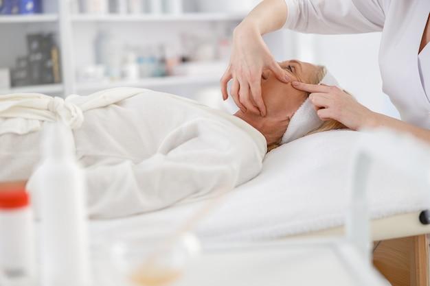 Ältere frau liegt auf dem rücken und bekommt eine gesichtslifting-massage. gesichtsmassage schönheitsbehandlung. wellness-, beauty- und entspannungskonzept.