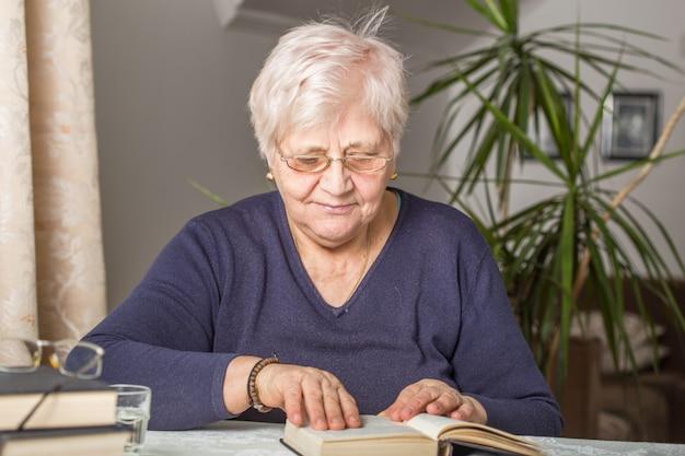 Ältere frau liest konzentriert in einem buch in der bibliothek im altersheim