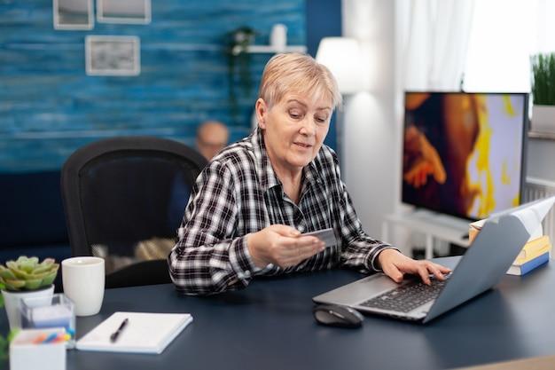 Ältere frau liest lebenslauf-code von der kreditkarte, die vor dem laptop sitzt