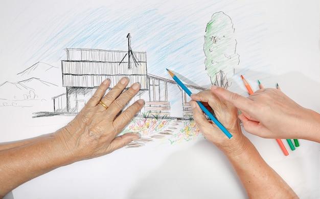 Ältere frau malt farbe auf ihrer zeichnung mit tochter, hobby zu hause at