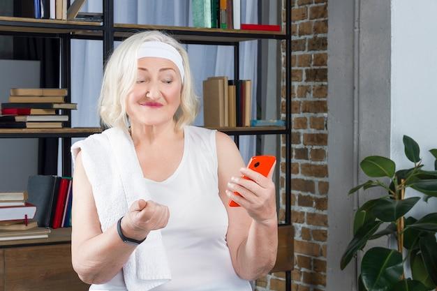 Ältere frau misst den puls per telefon