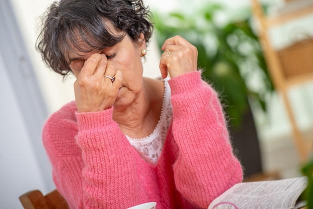 Ältere frau mit augenschmerz